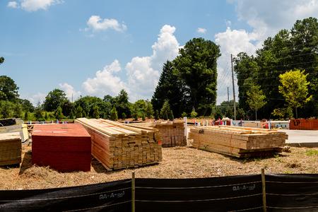 silt: Bundles of lumber beyond silt fence at a new home construction site