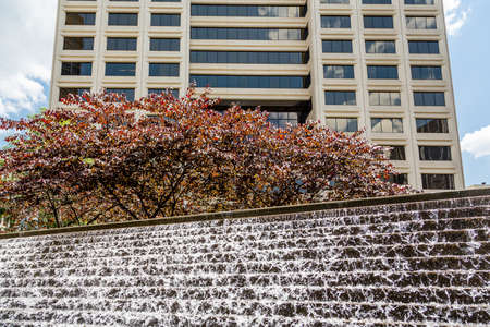 city park fountain: A Cascading Fountain Under Tree and Building in a city park