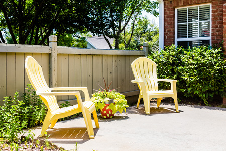 patio deck: Two yellow adirondack chairs on a patio by fence Stock Photo