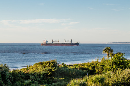freighter: A huge empty freighter off the coast in the tropics
