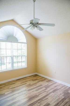New hardwood floor in an empty house with ceiling fan overhead