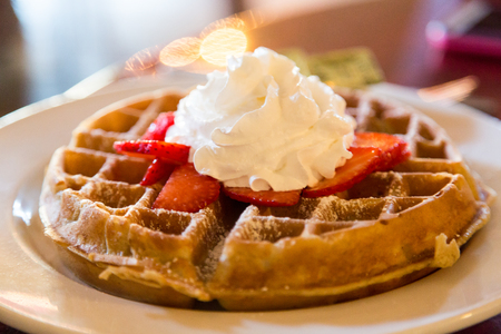 A golden waffle topped with strawberries and whipped cream