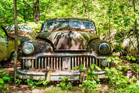 abandoned car: An old rusty car abandoned in the woods Stock Photo