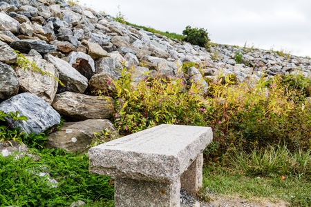 granite slab: An empty bench of granite slab by a rock wall Stock Photo