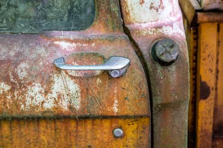 Old door handle on a rusty abandoned vehicle