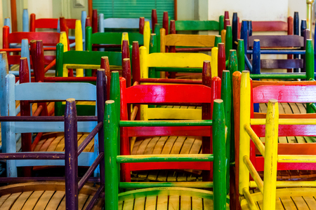 vintage furniture: Many Colorful Wood Chairs stacked in a corner
