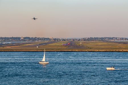 taking off: Sailboat and motorboat in Boston Bay by Logan airport with planes taking off and taxiing Stock Photo