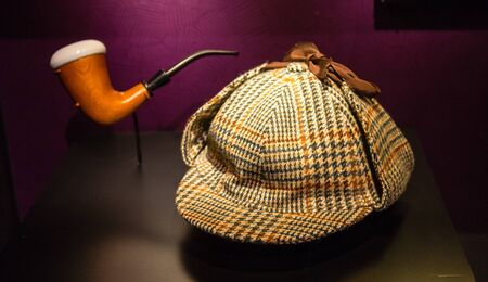 stalker: A houndstooth deer stalker hat and a briar pipe made famous by fictional detective, Sherlock Holmes