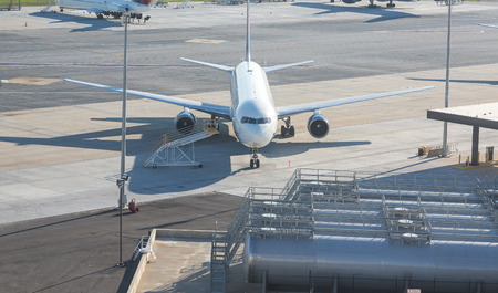 fuel tanks: A commercial airplane on the tarmac by fuel tanks