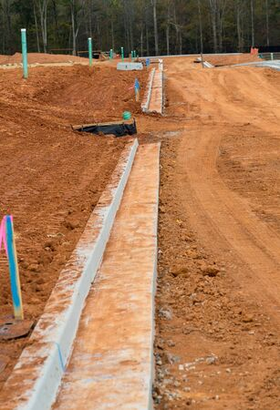grading: Dirt graded for roads in a residential construction site with new concrete curbs
