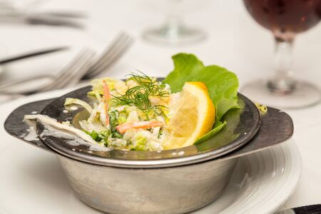 lemon wedge: A fresh seafood salad garnished with dill and lemon wedge Stock Photo