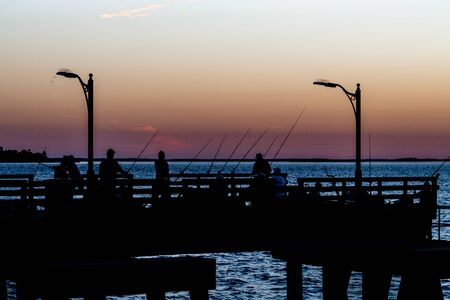 sillouette: A crowd of people fishing in sillouette at sunset Stock Photo