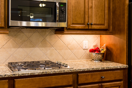 A new gas cooktop on a granite countertop with a tile backsplash Фото со стока