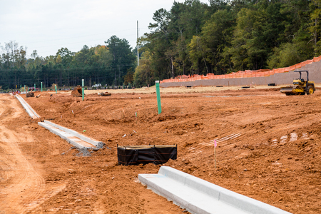 Dirt graded for roads in a residential construction site with new concrete curbs