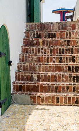 staircases: Old brick steps leading up besides a green, wooden door Stock Photo