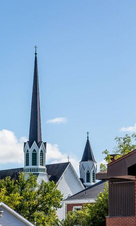 steeples: Two white church steeples on a blue sky