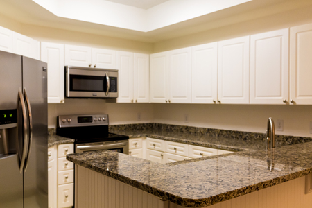 New stainless steel appliances and granite countertops with white wod cabinets