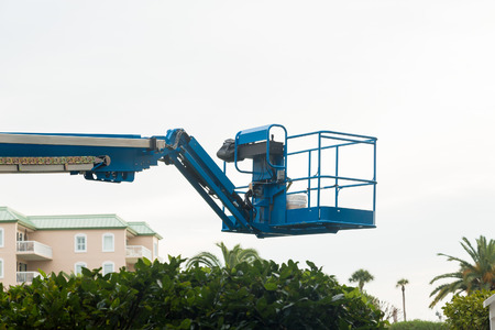Blue industrial lifting platform over tropical condos