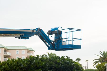 Blue industrial lifting platform over tropical condos
