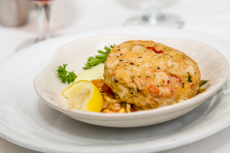 fresh food fish cake: Crab Cake with Lemon Wedge and parsley