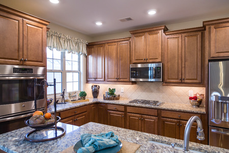 A new ktichen with wood cabinets, granite countertops and stainless steel appliances
