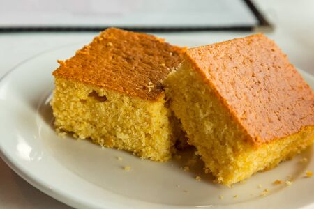 cornbread: Two pieces of cornbread on a white plate
