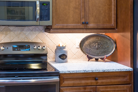 granite countertop: Decorations on Granite Countertop by Stainless Appliances Stock Photo
