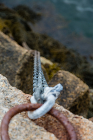 An old rusted iron ring and chain securing a ramp to a pier