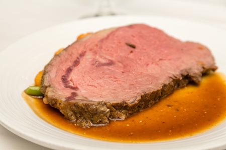 jus: A delicious slice of medium rare prime rib on a white plate with gravy or au jus