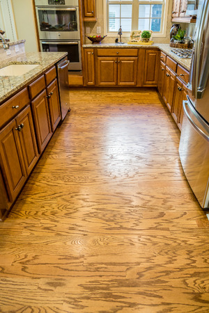 countertops: Shiny Hardwood Floor in New Kitchen with Granite Countertops and Stainless Steel Appliances