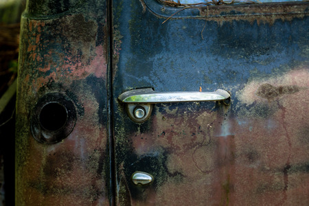 abandoned car: Old door handle on a rusty abandoned vehicle