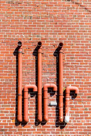 Red Vent Pipes op rode bakstenen muur