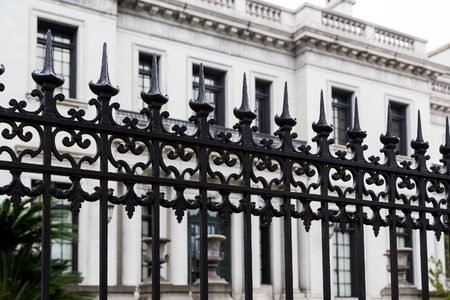 Black Wrought Iron Fence by White Building