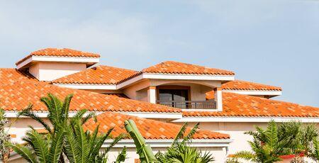 mediterranean homes: Orange Clay Tiles Under Blue Skies Beyond Green Palm Trees Stock Photo