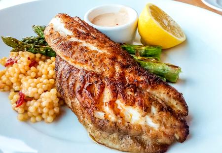 Zwartgeblakerde vis diner met couscous asperges en citroen Stockfoto