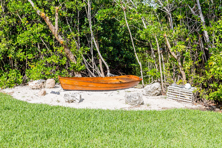 lobster boat: Old Boat in Sand by Lobster Trap by trees