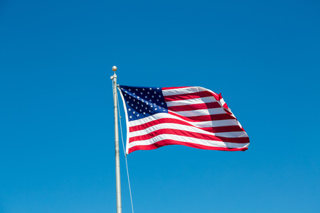 bandera americana ondeando en el viento en un cielo azul