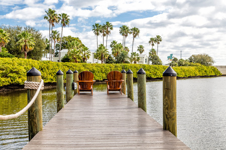 outdoor chair: Adirondack chairs on a wooden pier in the tropics Stock Photo