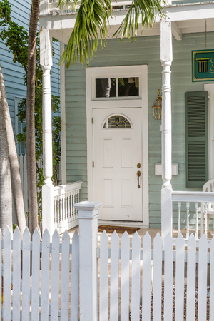 picket: Classic White Door Behind Picket Fence in tropics