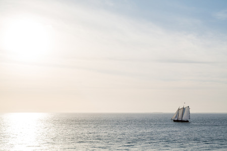 schooner: Schooner under sails sailing across a bay under beautiful skies