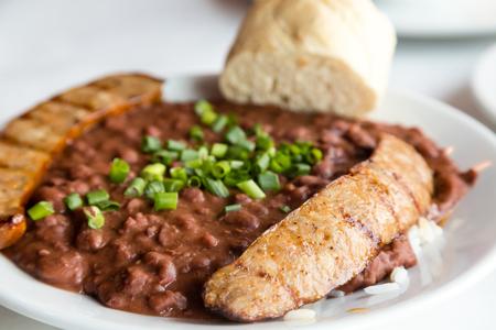 Salchicha con frijoles rojos y arroz cubierto con cebolletas verdes y pan francés