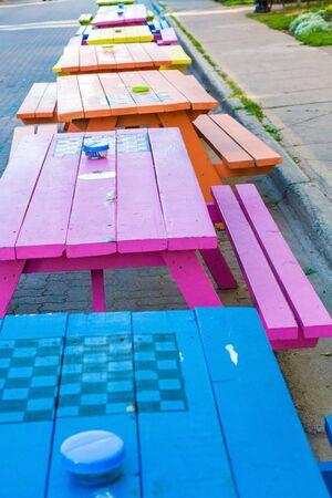 Une ligne de tables de pique-nique en bois coloré dans la rue à Charlottetown, Canada Banque d'images - 56083471