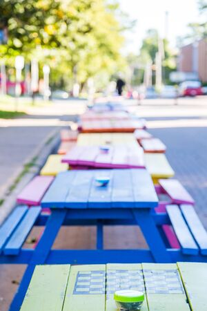 A line of colorful wooden picnic tables in the street in Charlottetown, Canada