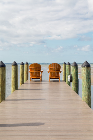 adirondack: Adirondack chairs on a wooden pier in the tropics Stock Photo