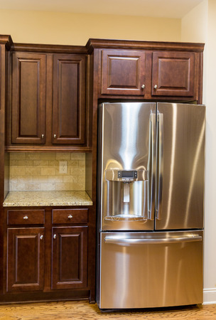 kitchen countertops: Stainless steel appliances, granite countertops and dark wood cabinets in a new kitchen