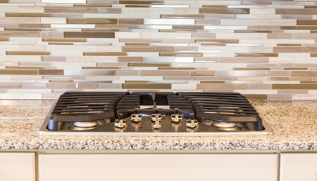 cooktop: Modern Gas Cooktop with Granite and Tile in new home Stock Photo