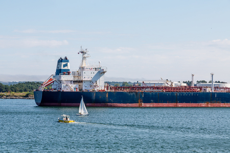 Sailboats cruising near a massive tanker Stock Photo