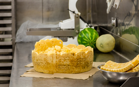 Cut Wheel of Cheese in Commercial Kitchen with melons in background Archivio Fotografico