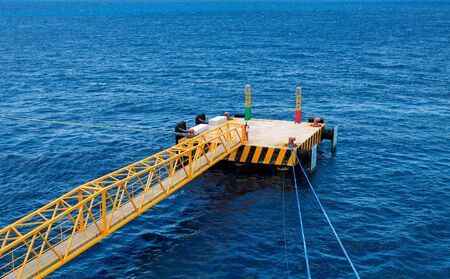 A yellow steel ganway over deep blue water in the Caribbean