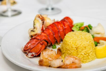 lobster tail: A lobster tail with shell, shrimp, rice and vegetables